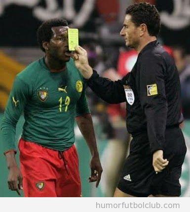 Árbitro pone la tarjeta amarilla en la cara del futbolista