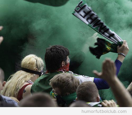 Aficionados en medio de un tifo con bengalas de humo verde