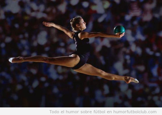 Foto de una bella gimnasta haciendo espagat en el aire con pelota gimnasia rítmica
