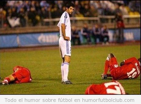 Foto Graciosa De Un Futbolista De Pie Y El Equipo Rival En El Suelo