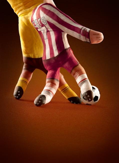Foto bonita de una mano pintada con dos jugadores de fútbol