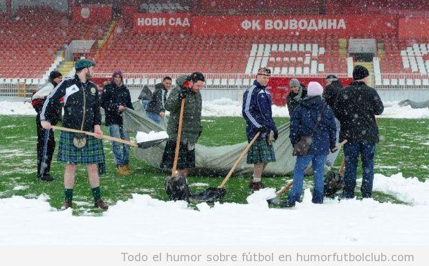 Aficionados de Escocia ayudando a los serbios a quitar nieve del campo