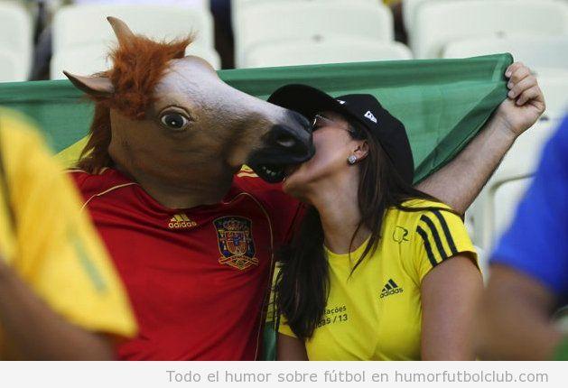 Foto bizarra, una chica besa a un chico con camiseta de España y cabeza de caballo en la Copa Confederaciones