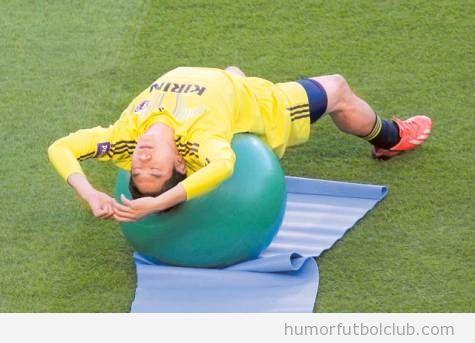 Imagen chistosa de jugadores japoneses estirando con balón de pilates