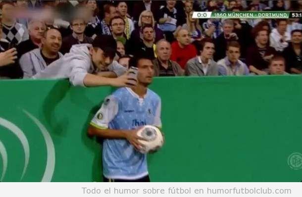 Foto graciosa de un aficionado sacando una autofoto con un jugador del Bayer de Munich en un saque de banda