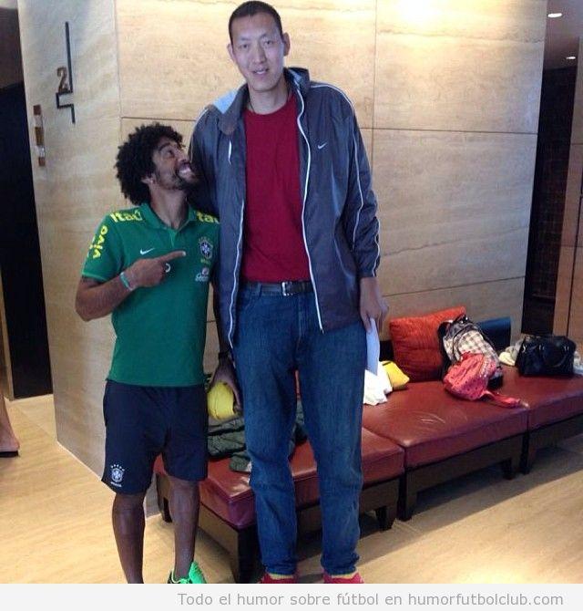 Foto graciosa del defensa de Brasil Dayne con el jugador de basket chino Sun Ming Ming