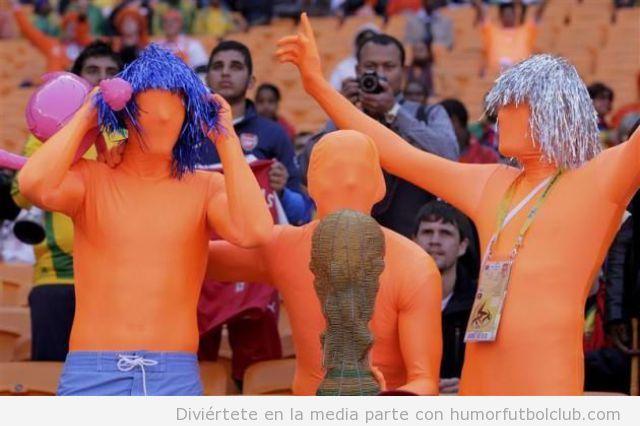 Afcionados o hinchas de la selección holandesa de futbol vestidos con mallas naranjas