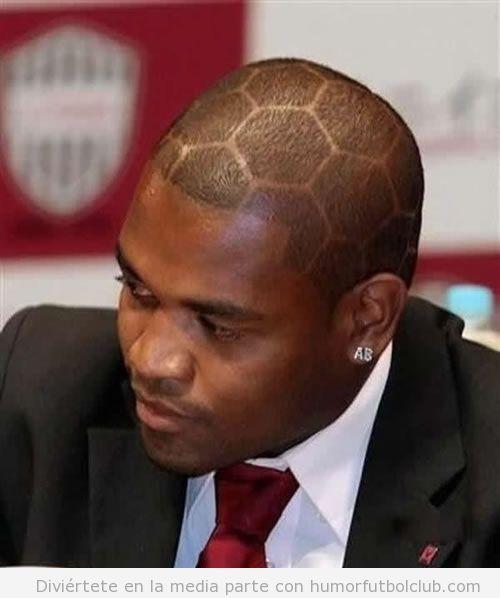 Futbolista con la cabeza rapada y el dibujo de un balón de fútbol