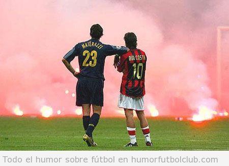 Dos futbolistas rivales esperan juntos a que se apaguen las bengalas del campo