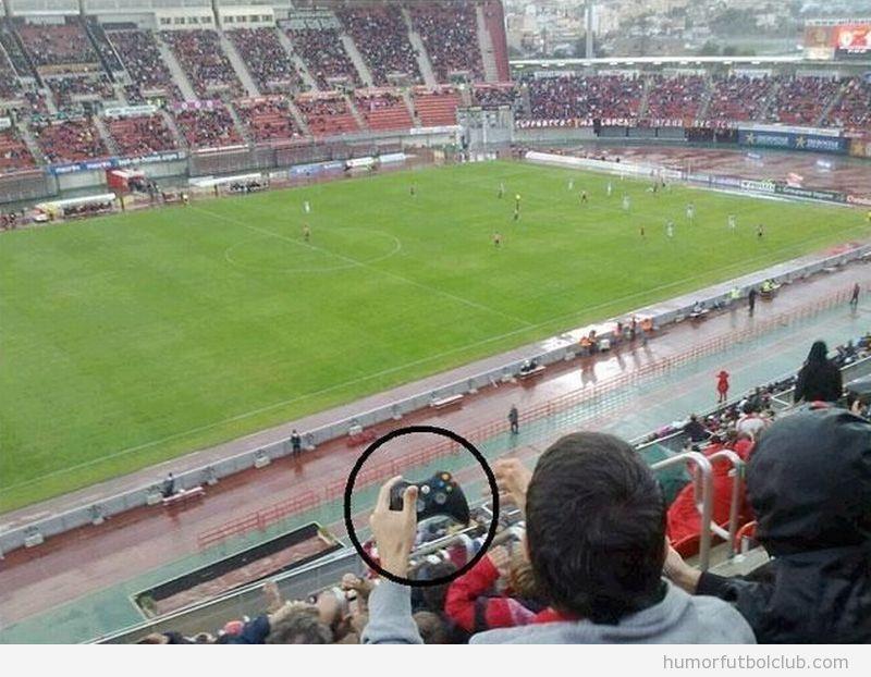 Chico con un mando de la consola en un campo de fútbol real