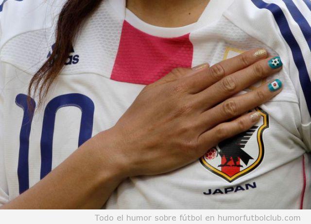 Jugadora de la selección femenina de fútbol de japón con la mano en el pecho y uñas pintadas