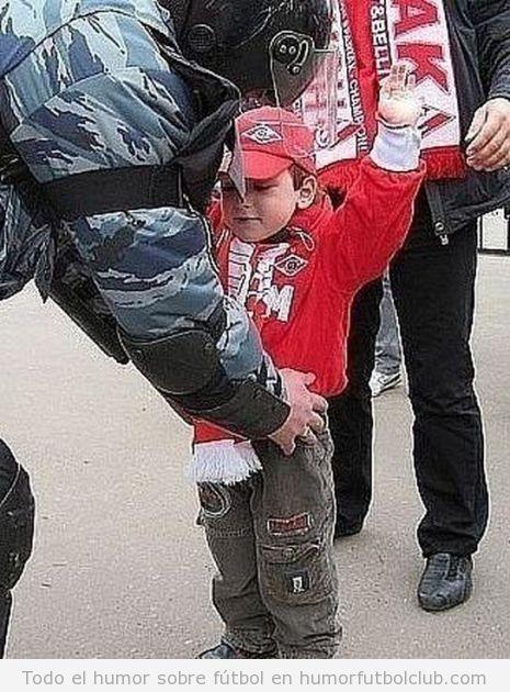 Niño pequeño es registrado o chequeado a la entrada de un campo de fútbol