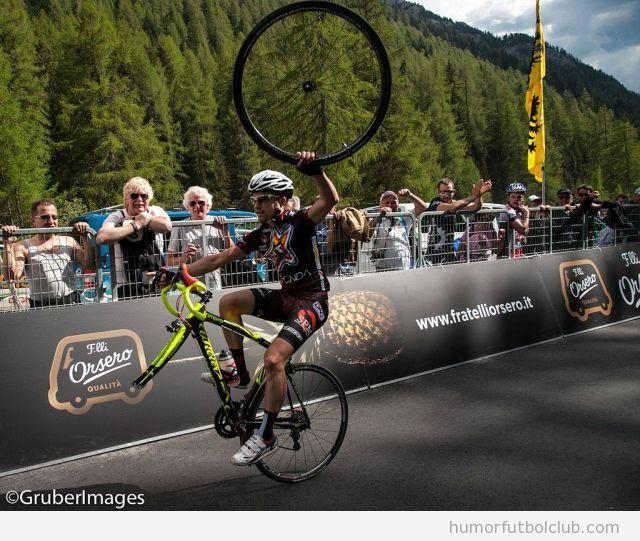 Foto graciosa de un ciclista sigue carrera con rueda delante en la mano