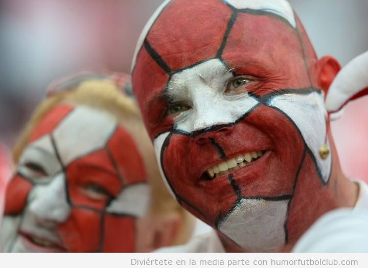 Aficionados de Polonia con la cara pintada como un balón de fútbol rojo y blanco