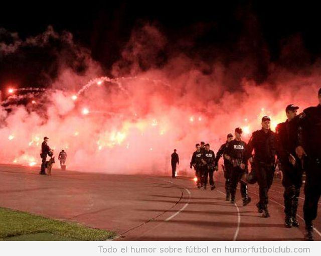 Tifo lleno de bengalas en u campo de fútbol con policia
