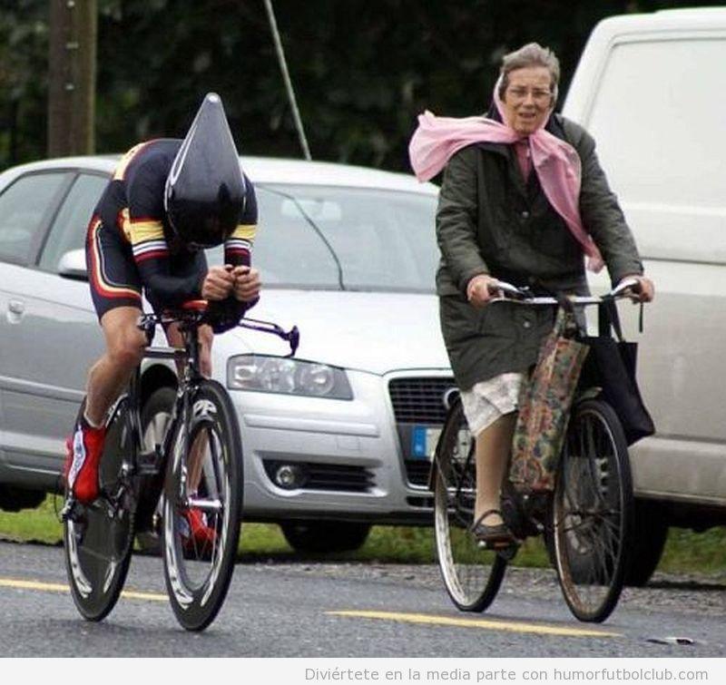 Foto graciosa de un ciclista profesional al lado de una abuela en bicicleta