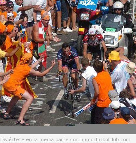 Aficionados hacen un fuck off o u corte de mangas a un ciclista mientras sube una cuesta en un tour