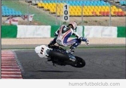Foto graciosa de un motorista en un circuito surfeando encima de la moto