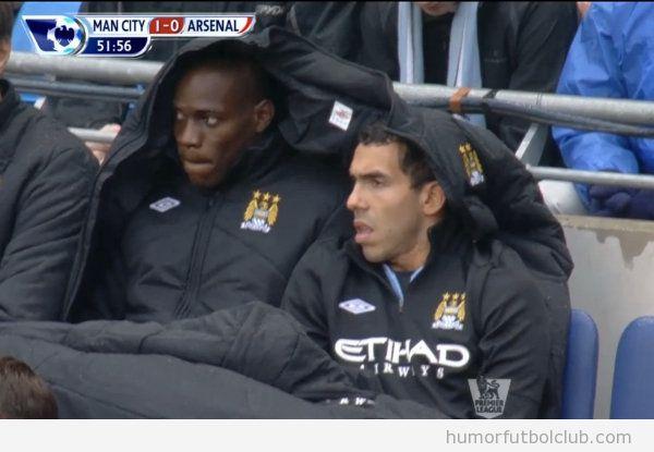 Mario Balotelli y Carlos Tevez comparten manta y anorak en el banquillo del Manchester City