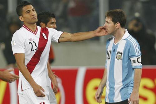 Un jugador de Perú toca la cara de Messi