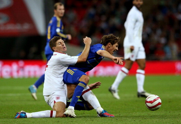 Seven Gerrard, de inglaterra, da un rodillazo en el traseo a Denys Grmash, de Ucrania