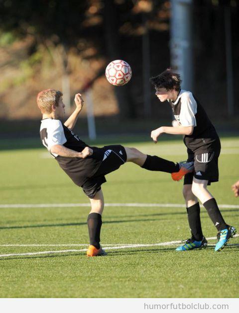 Foto graciosa de dos chicos jugando a fútbol, patada en los huevos