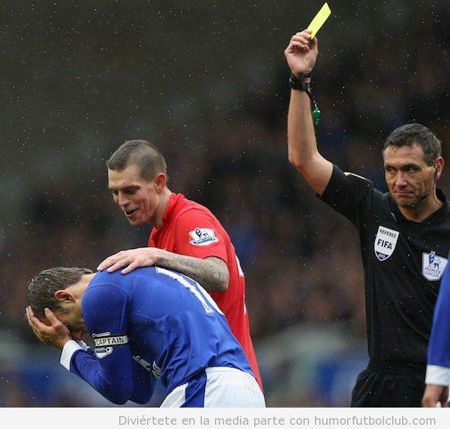 Daniel Agger consuela y se ríe de Neville en una tarjeta amarilla en el Liverpool Evertoon