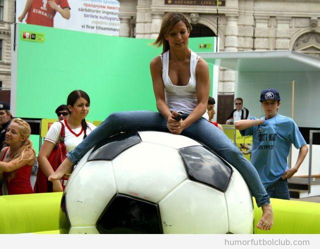 Foto de una chica sexy subida encima de una pelota gigante de fútbol que bota