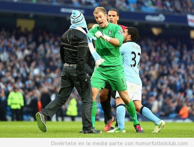 Joe Hart, portero del Manchester Cirty, defiende a Rio Ferdinand de ser atacado por un fan del City