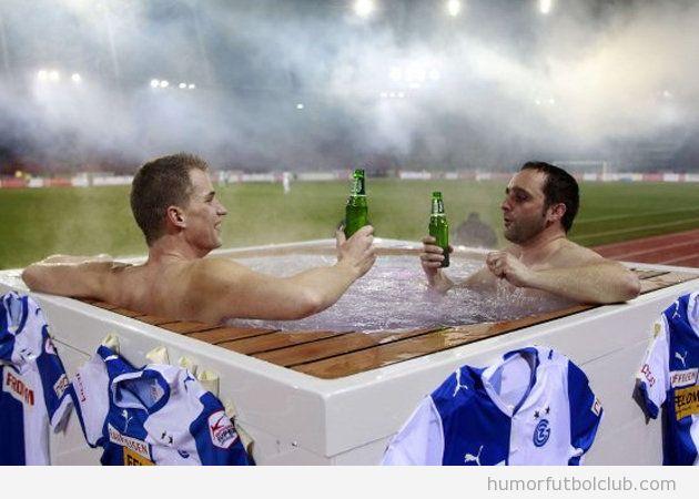 Dos aficionados del Grasshopper Zurich ven el partido en directo en un jacuzzy coon cerveza