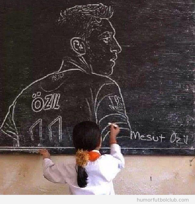Una niña dibuja un retrato de özil en la pizarra de clase