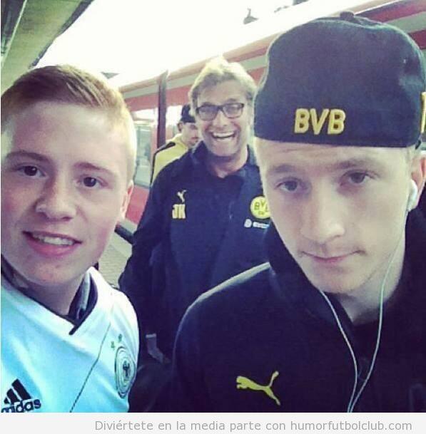 Foto graciosa de Jurgen Klopp haciendo de jodefotos a aficionados del Borussia Dortmund