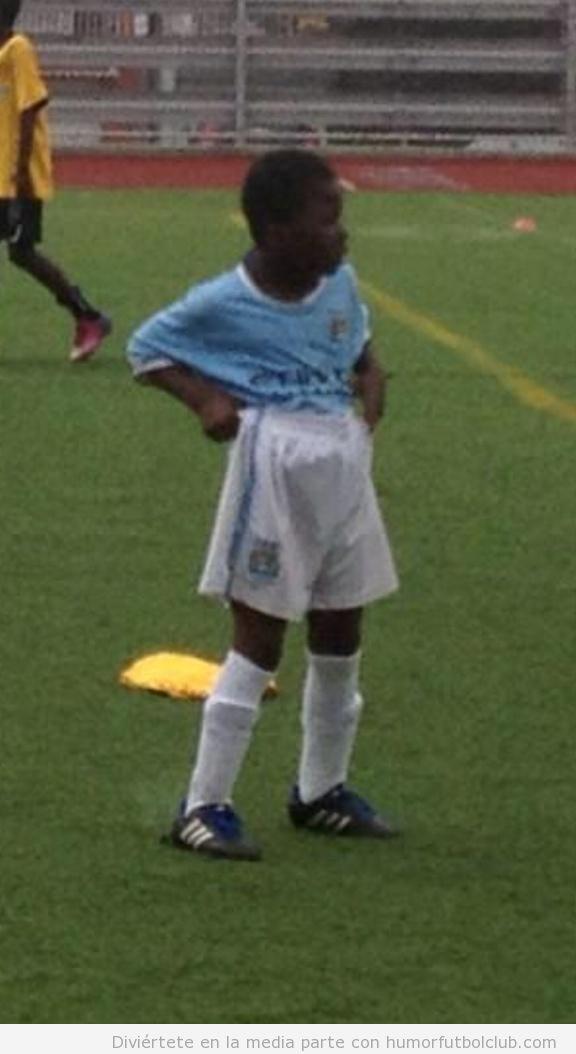 Foto graciosa niño futbolista con la camiseta por dentro