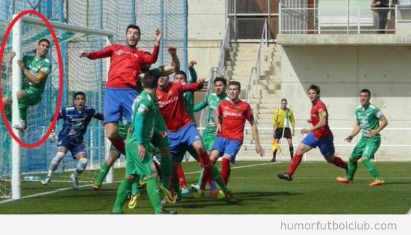Foto graciosa de un defensa subido al poste para defender un corner
