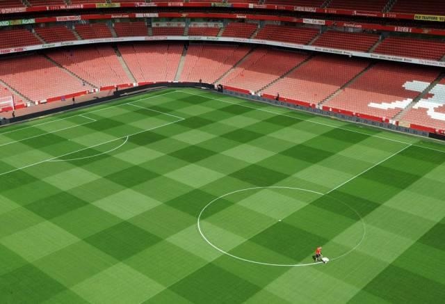 Foto de un hombre pintando las líneas de un campo de fútbol