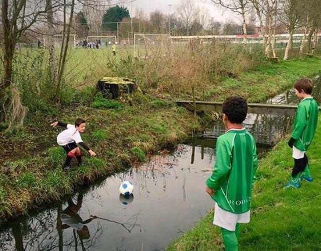 Foto graciosa niños , jugando a fútbol, pelota en el río